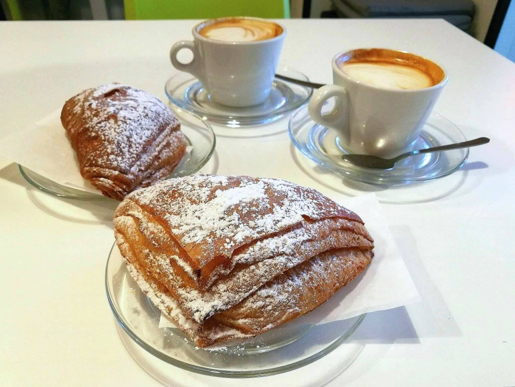 Two powdered Italian croissants and two cappuccino