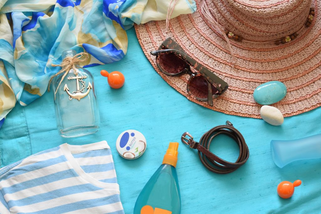 vegan sunscreen, hat, and sunglasses on blue towel