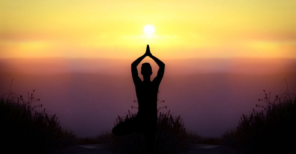 Person doing yoga with the sunrise