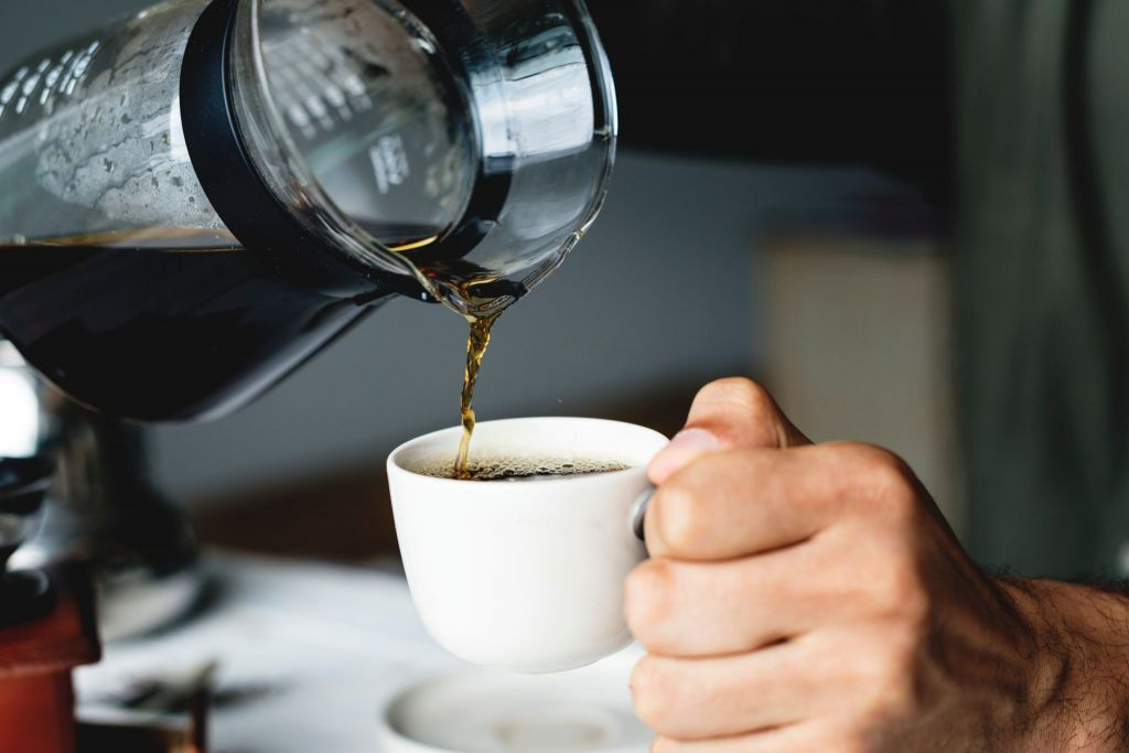 man pouring black coffee into mug